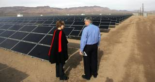 Yvonne Szymczak, left, and Brok Armantrout look at more than 167,00 solar modules over 80 acres of land at El Dorado Valley at Sempra Energy's new El Dorado Energy Solar facility on Thursday.