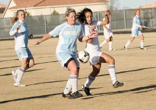 Liberty forward Minerva Mnassis (8), right, vies for the ball with a Foothill defender during a home game on Jan. 9.
