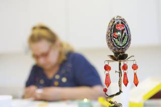 A Ukrainian Easter egg deorated with a poppy, the national flower of Ukraine, is displayed as an example while Dee Poya, 65, creates an egg during the Pysanky craft class held at the Henderson Senior Center Tuesday.