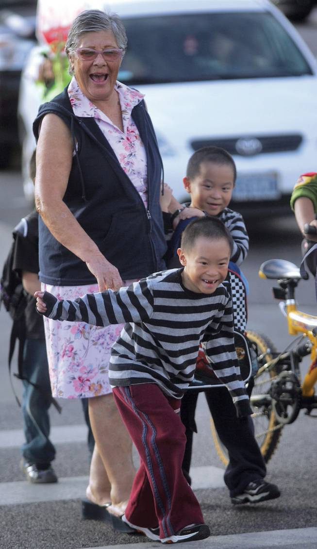 From left to right, babysitter Gloria Cohen walks Dai-Quy and Dai-Nien Tran home from school. Givens is one of nine Summerlin schools that might go from a nine-month to a year-round schedule to alleviate crowding.