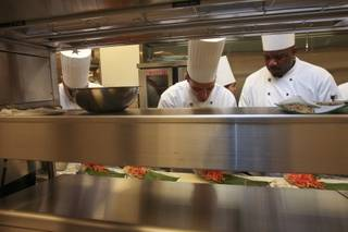 Chefs work together to prepare food behind the line in the main kitchen during a preview of restaurants at M Resort.