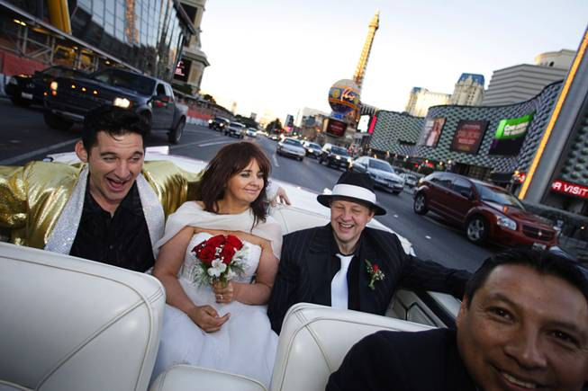 Elvis impersonator Roddy Ragsdale entertains Lynn Hassell, 46, and Neil Cawkwell, 45, of Ascot, England, as they ride back to their hotel after being married at The Little White Wedding Chapel on The Strip on Thursday, Jan. 28, 2010. Driver Oscar Oscar Villegas is at right.