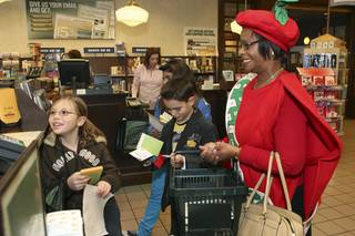 At the conclusion of their Barnes & Noble shopping spree Wednesday, from left, Faith Teagarden, JamiLynn Merolle, Keegan Tharp and Principal Deborah Harbin pay for their books with the $25 gift cards they received as a reward for winning the Elise Wolff Elementary School APPLE Core reading program.