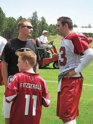 Arizona Cardinals' quarterback Kurt Warner, right, visits with former college teammate Jake Kothe and his son, Elijah, left foreground.