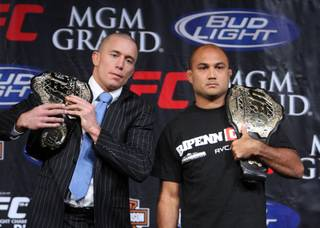 UFC welterweight champion Georges St. Pierre, left, of Montreal, Quebec, Canada and lightweight champ B.J. Penn of Hilo, Hawaii pose with their title belts during a news conference Wednesday, January 28, 2009 at MGM Grand. St-Pierre and Penn headline Saturday night's UFC 94 card in a rematch of their first fight, which St. Pierre won by split decision three years ago. While both fighters could likely make the UFC Hall of Fame one day, a win by Penn would make him the first UFC fighter to hold two titles in two different weight classes at the same time.