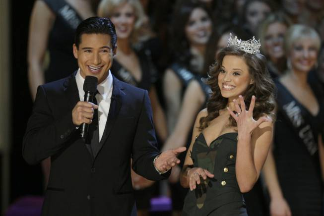 Katie Stam, Miss America 2009, shows off her engagement ring as host Mario Lopez looks on during the 2010 Miss America Pageant at Planet Hollywood.