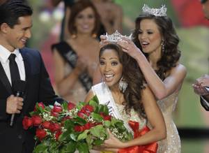 Miss Virginia Caressa Cameron reacts as she is crowned by 2009 Miss America Katie Stam during the 2010 Miss America Pageant at Planet Hollywood. Host Mario Lopez, left, looks on.