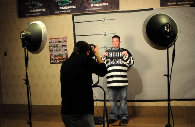"John Grote gets his photo taken at the prison booth during ""Rod Blagojevich Prison Uniform Night"" Friday as the Wranglers take on the Bakersfield Condors at the Orleans Arena."