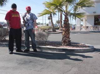 Friends Guillermo, left, and Saul, who did not want to give their last names, stand over the spot where their friend, a 21-year-old man known as