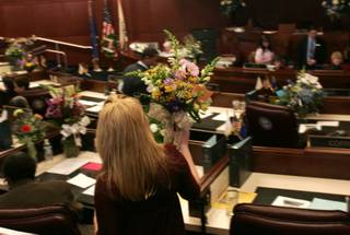 A legislative assistant delivers flowers to the Senate floor on the first day of the 2009 legislative session Monday in Carson City.