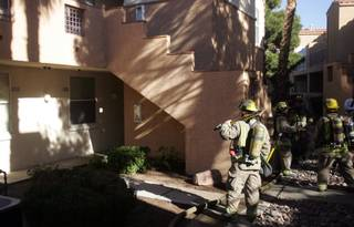 Firefighters gather outside the Cha Cha Cha Apartments, 640 E. Horizon Drive, after extinguishing a small patio fire Monday. The fire was quickly controlled without any damage to other units.