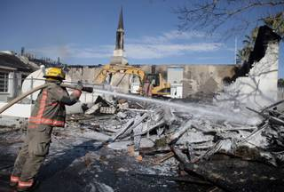 Firefighters spray water on the remains of the Church of Jesus Christ of Latter-day Saints in Logandale on Wednesday. Clark County fire spokesman Scott Allison said there was no immediate indication of foul play in the 4 a.m. fire that engulfed the church.