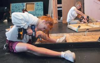 Callae Waller, left, and Sasha Vancura work on the two-story set of Faith Lutheran's upcoming play,