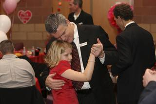 Lily Pellegrini, 9, enjoys a slow dance with her father, Luciano, at the Father-Daughter Valentine's Day Dance at Alexander Dawson School at Rainbow Mountain on Friday.