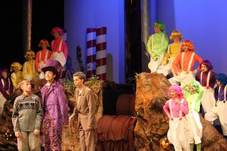 Barry Fortgang, a junior, plays Willy Wonka, second from the left, as he show Tanner Nelson, a sophomore playing Charlie Bucket, his chocolate factory during Friday's performance of