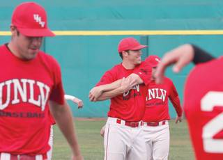UNLV pitcher Stephen Singer, center, smiles during warm-ups at the Rebels' baseball practice.