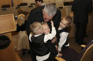 Judge David Gibson receives congratulatory hugs from his three grandsons, from left: Thomas Anderson, Jared Lamoreaux, Jr., and Nathan Anderson. Gibson was sworn in as Justice of the Peace during the Investiture Ceremony Thursday at Henderson City Hall.