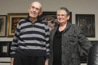 Howard and Helene Moore lead a tour of the 800-piece kissing art collection in their home for members of the Henderson Senior Center on Wednesday.