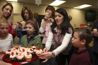 Second-grade teacher Lisa Aquino selects a Valentine's Day cupcake delivered as a gift by Freed's Bakery Friday morning at Glen Taylor Elementary School. Teachers' children were present for the celebration.  From left: Austin Almeido, Lisa Aquino, Shelly Soule, Arabella Carter, Renee Colvin, Marie Almeido and Alexis Almedio.