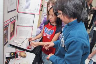 Fifth-grader Cristobal Lledo demonstrates the conduction of electricity using fluids, fruits and vegetables for third-grader Tina Ngo, right, during the fifth-grade science fair at Selma Bartlett Elementary School.