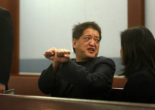 Terrance K. Watanabe, 52, of Omaha, Neb., talks with a woman (identified as a sister) and attorneys before his appearance in court at the Regional Justice Center in Las Vegas on Wednesday. Watanabe, in a negotiated deal, posted $1.5 million and turned himself in for processing. According to prosecutors, the high-rolling philanthropist owes $14.7 million to Caesars Palace and the Rio, which are owned by Harrah's Entertainment Inc.