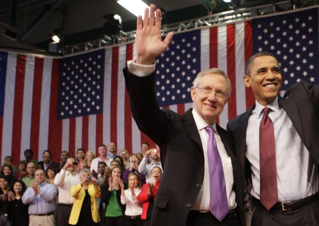 Senate Majority Leader Harry Reid, left, and President Barack Obama wave as they conclude a town hall meeting Friday, Feb. 19, at Green Valley High School in Henderson.