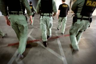 Members of Metro Police's vice unit walk from the parking garage to the service elevators of a Las Vegas Boulevard condo tower in 2009 to search the condominium of a suspected pimp.