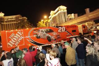 Joey Logano's car hauler passes by fans during a parade of NASCAR haulers on the Las Vegas Strip on Thursday, Feb. 25, 2010.