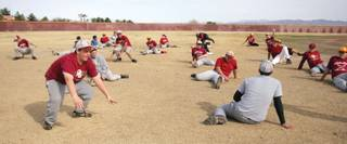 Members of the Del Sol baseball team stretch out at the beginning of practice.