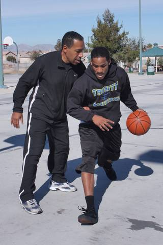 Budweiser Hawkins III, right, a junior guard for Trinity Christian and his father Budweiser Hawkins II play basketball together at Desert Bloom Park.