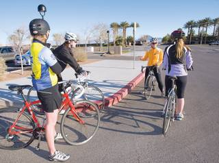 Jackie Arcana (in orange) reviews some safety tips before leading a bike ride.