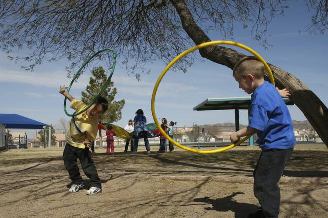 Kindergartners Kyle Lobaugh and Stryder Brown, right, twirl hula hoops on their arms during kindergarten field day Friday at John Dooley Elementary School.
