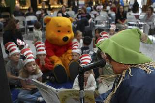 Children listen to The Scarecrow, played by Terri Hacker, read stories Saturday during the grand opening of Henderson Libraries' new branch inside the Galleria at Sunset Mall.