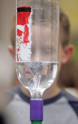 Riley Thompson, 8, watches as water twirls through a soda bottle like a tornado during John R. Beatty Elementary School's Jr. Engineering Day.