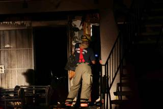 Two people were hospitalized for smoke inhalation Thursday night after a couch caught fire outside their northeast Las Valley Valley home.