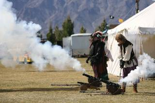 Steve Baer, right, and Nathanial Davidson set off black powder cannons during the Renaissance Faire at Veterans Memorial Park on Friday. The event runs through Sunday.