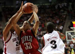 Tre'Von Willis goes to the basket by two defenders during  first-half action as the Rebels take on the San Diego State Aztecs Saturday night, March 7, 2009, at Cox Arena in San Diego.  UNLV lost 57-46 to finish the regular season 9-7 in conference play.