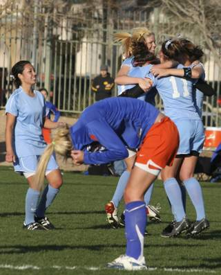 As Centennial High School's players, in light blue, celebrate their 2-0 victory at the Sunset Regional championship Monday, Bishop Gorman's Cassie Downs, foreground, tries to hide the tears of defeat.