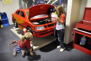 Brianna Reed, left and Abigail Johnson, tend to the vehicle inside the car exhibit the newly opened Green Village display at the Lied Discovery Childrens Museum on Tuesday, March 10, 2009. The 3,500 square-foot mini-city has an environmentally friendly focus that includes exhibits with lessons in everyday living and environmental sustainability.