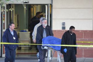 Valley Funeral Home attendants remove the body of the man who police say they shot after he threatened them with a gun. The emergency room at St. Rose - Siena Hospital, where the shooting took place, remained closed Wednesday morning.