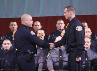 Henderson Police Cadet Ronald Feola, right, is awarded the valedictorian by TAC Officer Dave Adams during the graduation ceremony of the Southern Desert Regional Police Academy Thursday.