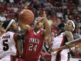 UNLV center Shamela Hampton reaches for a rebound between San Diego State guard Jene Morris, left, and forward Jen Layton-Bailes during the semifinal game at the Mountain West Conference Basketball Championships Friday, March 13, 2009.  San Diego State won the game 71-63.