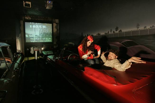 The Amazing Jonathan and assistant Erica Vanlee sit in one of the magician's cars at his indoor drive-in theater, which has been made to look like the Detroit drive-in where he worked in the '70s and '80s.