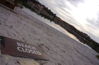 A sign indicating the beach is closed rests on the shore of Lake Las Vegas.