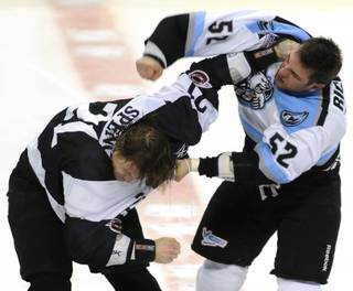 Wranglers left winger Tim Spencer, left, turns away from a right hand thrown by Aces winger Robin Richards as the two dropped gloves four seconds into the game at the Orleans Arena on Saturday night.