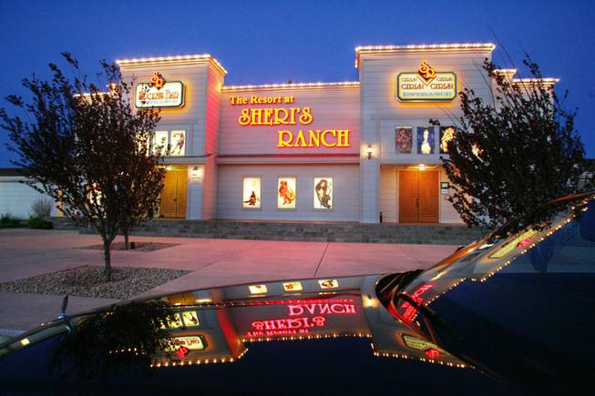The lights of Sheri's Ranch in Pahrump are reflected in the hood of a limousine parked in front.