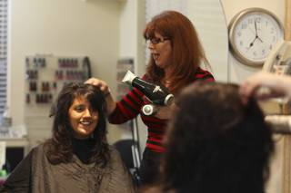 Destinee, 13, visits with Cookie Seminario, right, while having her new haircut styled Monday during
