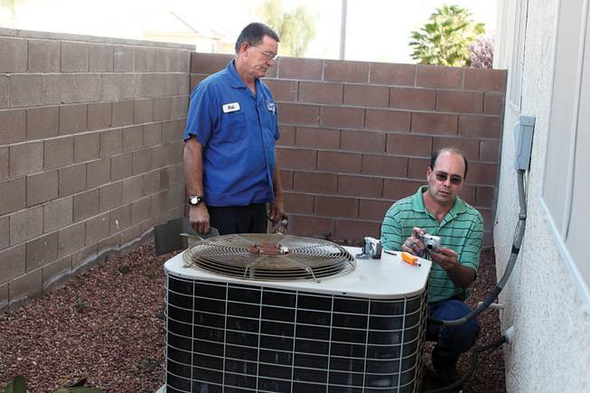 Technician Rich Parker, left, and Jack Ramsay of Sierra Air Conditioning check out a unit at a house involved in a lawsuit. Ramsay is there because he received notice from the builder, which had received a letter from the homeowner's attorney complaining of problems.
