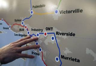 Andrew Mack, chief operating officer of DesertXpress Enterprises, points out California high-speed rail routes during a news conference for the DesertXpress high-speed rail project March 25, 2010. A line from Victorville to Palmdale could tie DesertXpress to the California high-speed rail line.