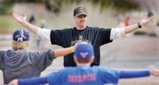 Al Kermode, coach of the Little League Diamond Backs, leads his team in some stretching exercises during a morning practice at the Boulder City Veterans Memorial Park ball fields.